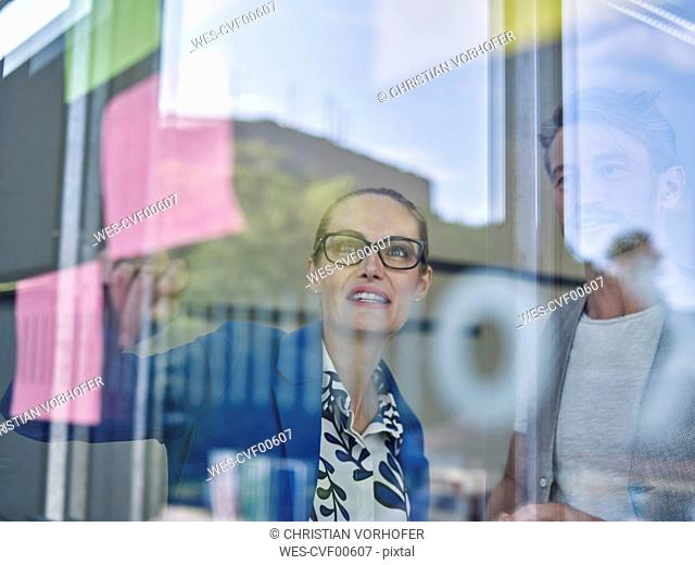 Colleagues looking at sticky note at glass pane