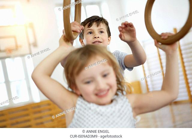 Children swinging from gymnastic rings