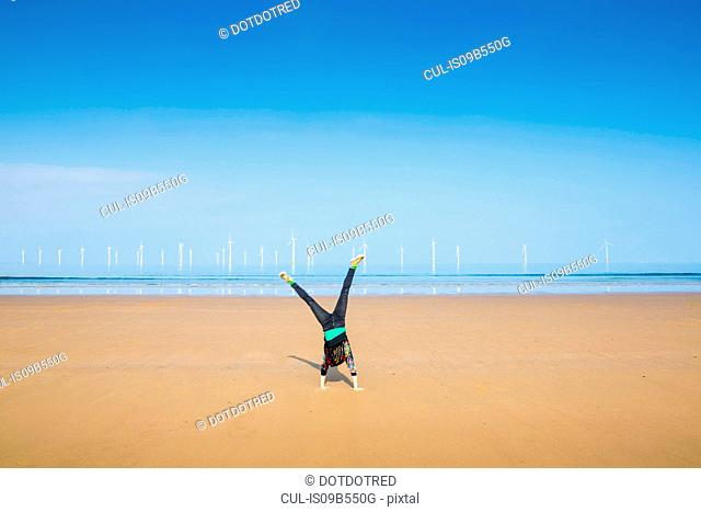 Mature woman doing cartwheel on Redcar beach, North Yorkshire, UK