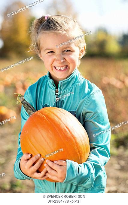 Girl holding a pumpkin in a pumpkin patch with a big smile; Trenton, Ontario, Canada