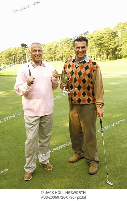 Portrait of two mature men holding a trophy and golf clubs