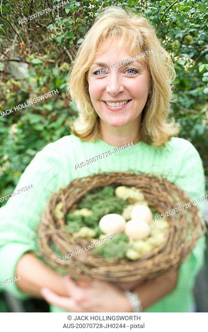 Portrait of a mature woman holding a bird's nest with eggs