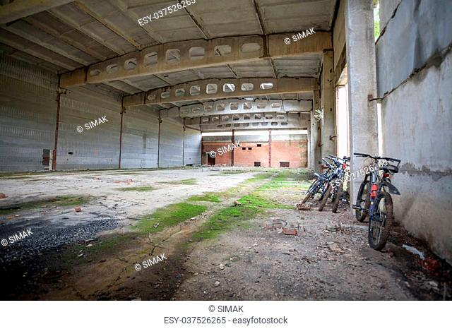 Large industrial, military empty hangar. Mountain bikes near the wall