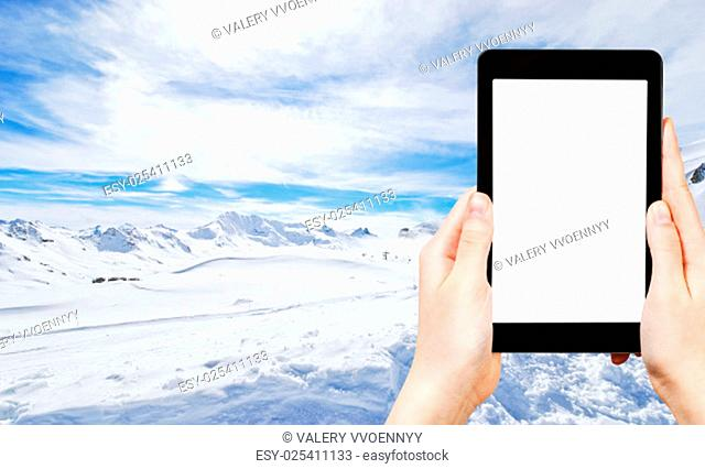 travel concept - tourist photograph mountain skiing on Alps in Paradiski region, Val d Isere - Tignes , France on tablet pc with cut out screen with blank place...