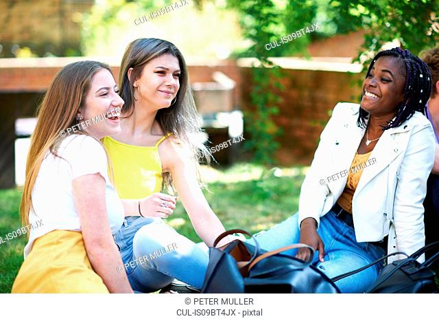 Female higher education students chatting on college campus lawn