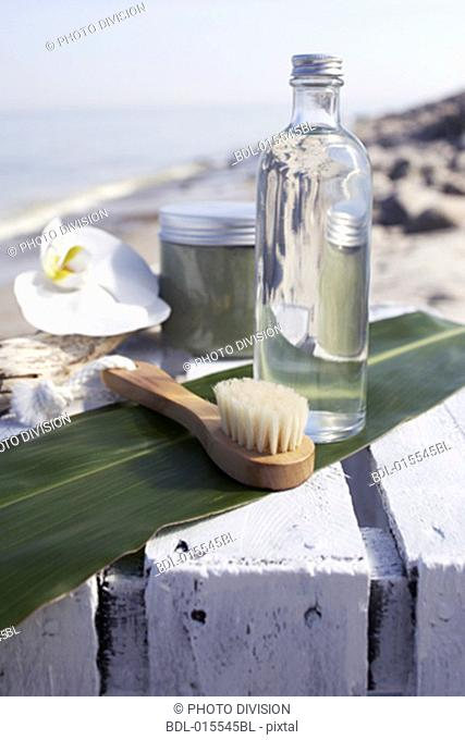 still life of brush and bottle with lotion on beach