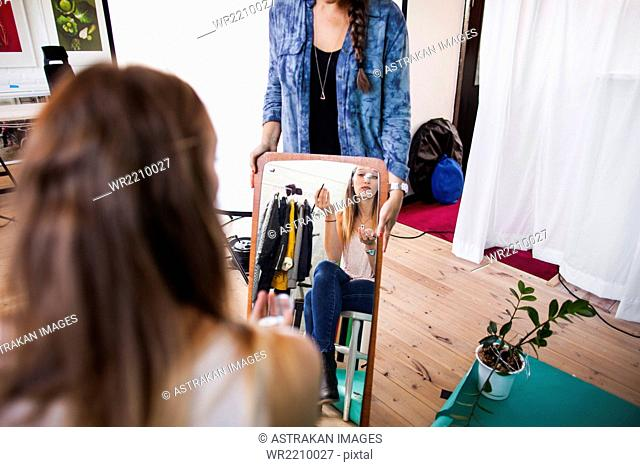 Midsection of photo assistant holding mirror for fashion model applying make-up in studio