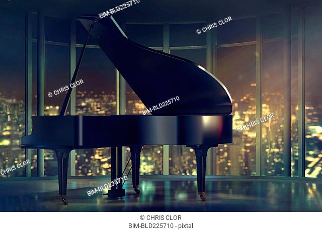 Grand piano near window with scenic view of city