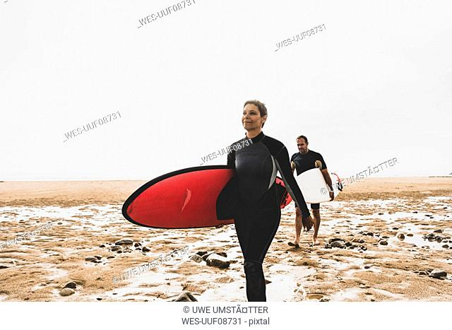 France, Bretagne, Crozon peninsula, couple walking on beach carrying surfboards