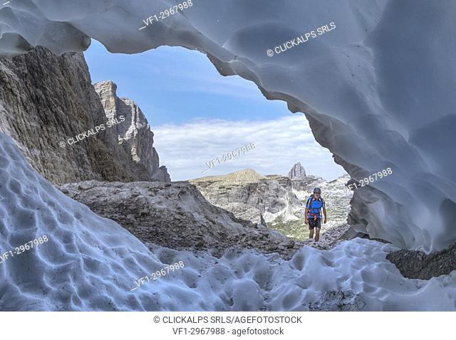 Italy, South Tyrol, Hocpustertal, Sexten. Snow cave in the summer season along the Alpinisteig / Strada degli alpini via ferrata, Sexten Dolomites