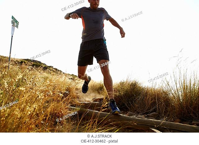 Male runner descending trail hillside
