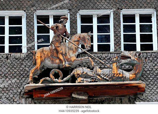 Old wooden statue high on a house of Saint George killing the dragon