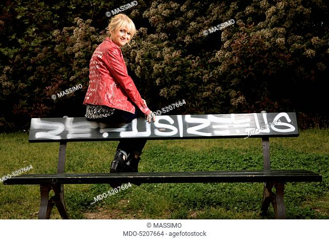 Actress and comedian Luciana Littizzetto sitting on the back of a bench inside the public park Parco del Valentino. Turin, Italy. 21st April 2016