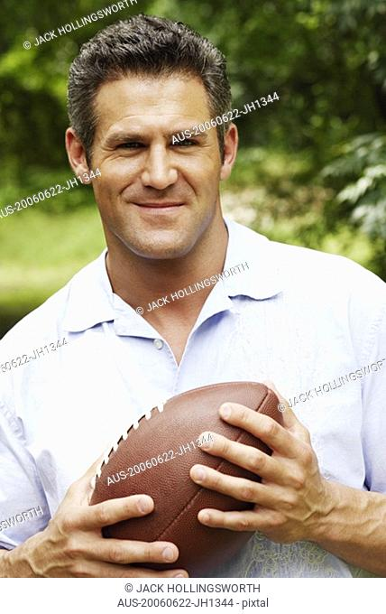 Portrait of a mid adult man holding a football