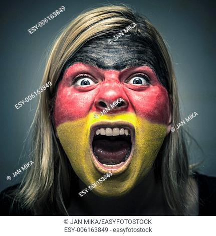 Portrait of angry woman with flag of Germany painted on face
