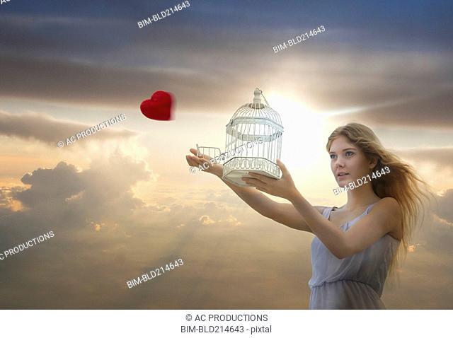 Caucasian woman releasing heart from birdcage