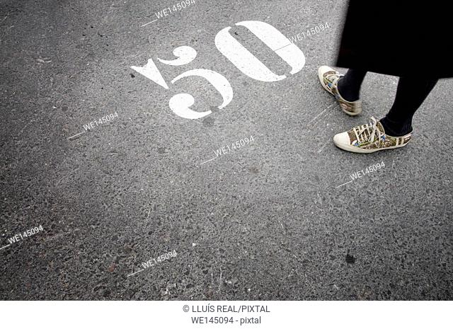 woman feet in front of a number 50 painted on the asphalt