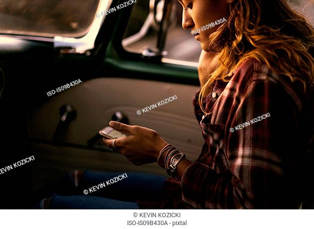 Young woman looking at smartphone in front seat of pickup truck at Newport Beach, California, USA
