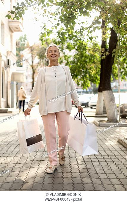 Smiling senior woman walking on pavement with shopping bags