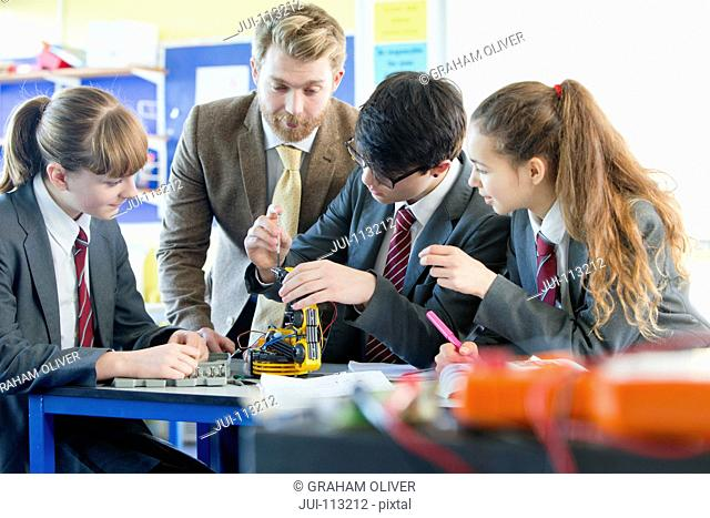 Teacher guiding high school students assembling robot in science class