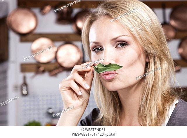 Italy, Tuscany, Magliano, Close up of young woman smelling basil leaf in kitchen, portrait