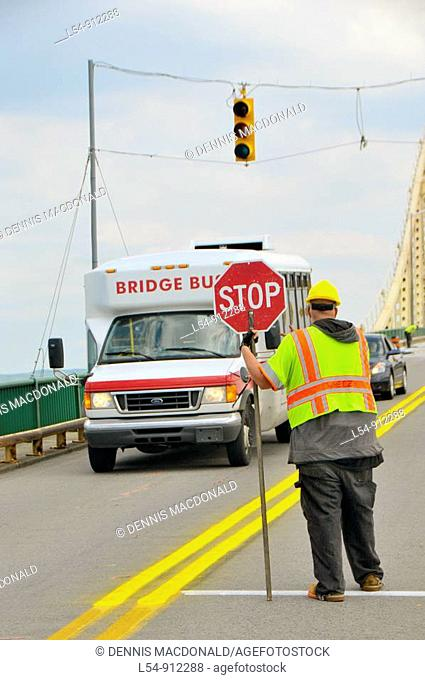 Construction Worker Controls traffic on International Bridge connecting Sault Ste  Marie Michigan USA and Sault Ste  Marie Ontario Canada