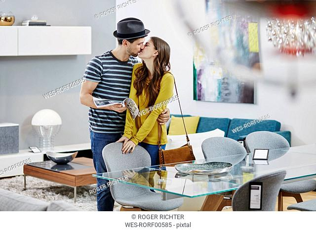 Couple in furniture store looking at dining table, kissing