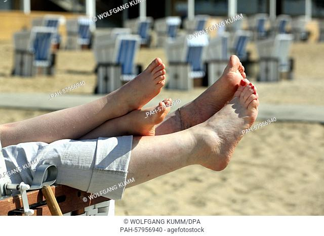 Two large and two small feet poke out of a canopied beach chair at the start of swimming season at Wannsee Beach in Berlin, Germany, 01 May 2015