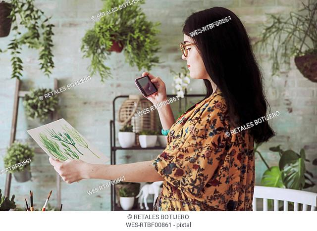 Young woman taking pictures of painted plants with her smartphone