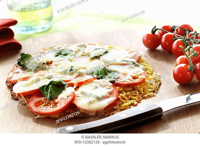 A pizza rosti with tomatoes, mozzarella and basil