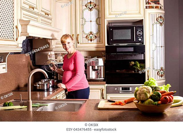 Pregnant woman is cooking dishes in the kitchen