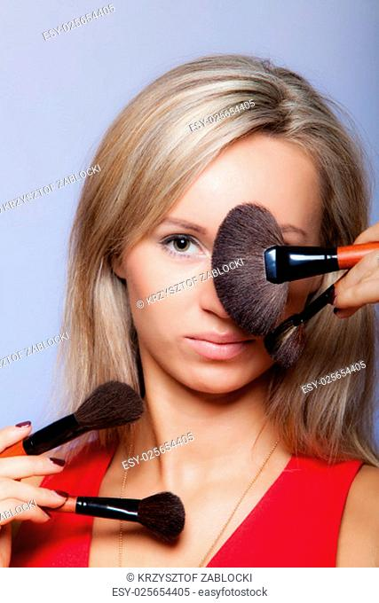 cosmetic procedures and beauty makeover concept. attractive woman red dress holds professional makeup brushes near face. make-up applying tools with accessories