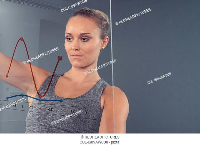 Young woman looking at chart on glass wall, grey background