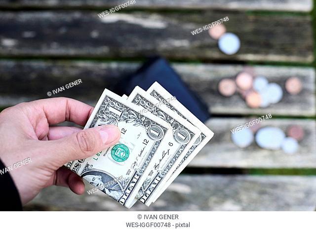 Hand holding one dollar bills