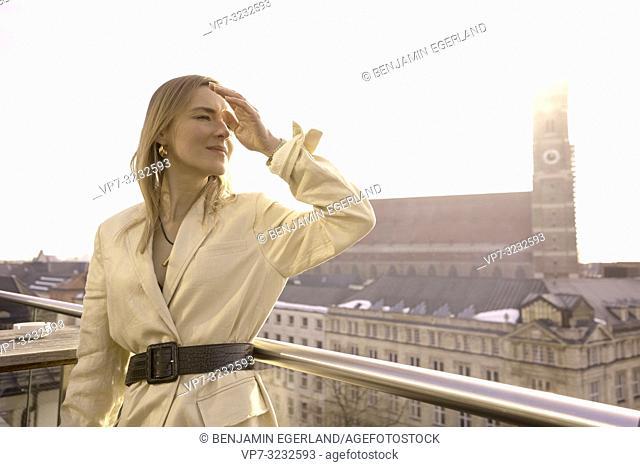 fancy blogger woman on balcony next to church Frauenkirche, Marienkirche, in Munich, Bavaria, Germany