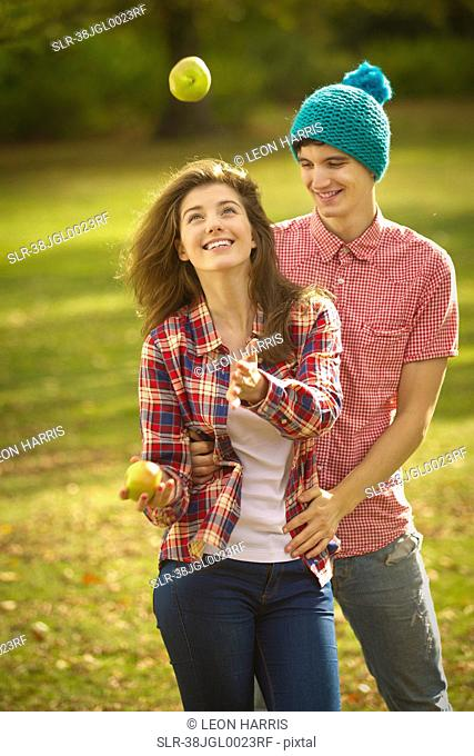 Teenage couple juggling apples in park