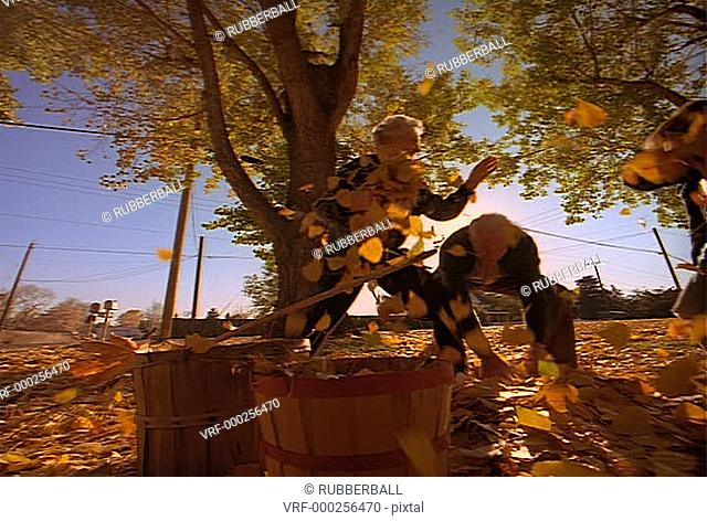 wide tracking shot of two grandparents playing in the colorful autumn leaves with their grandson