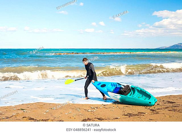 Young handsome man carrying kayak at sea beach
