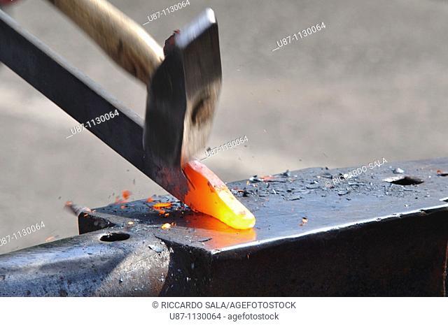 Blacksmith forging a red hot piece of iron