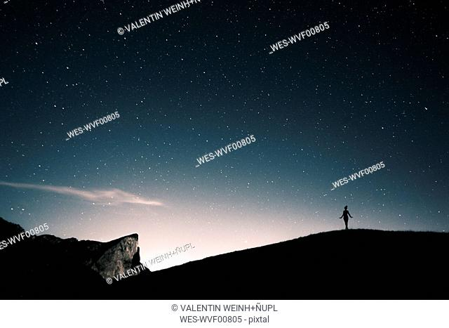 Austria, Mondsee, silhouette of woman standing under starry sky