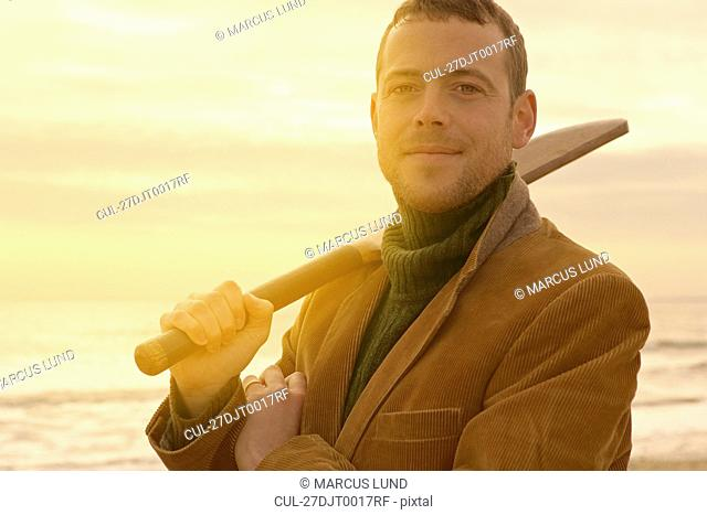 Man on beach with old cricket bat