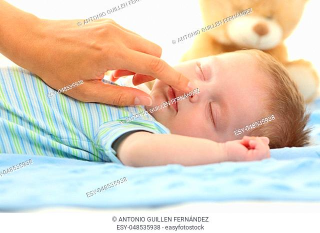 Mother hand touching the nose of a baby sleeping on a bed
