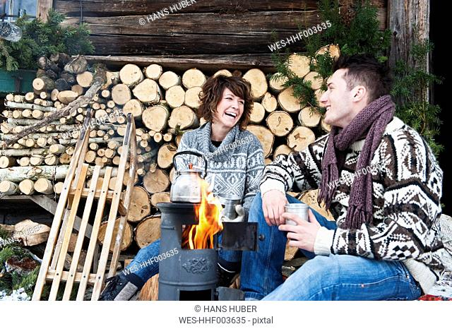 Austria, Salzburg Country, Flachau, Young man and woman making tea and sitting besides stove in winter