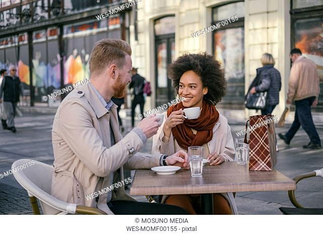 Happy couple having a coffee in the city