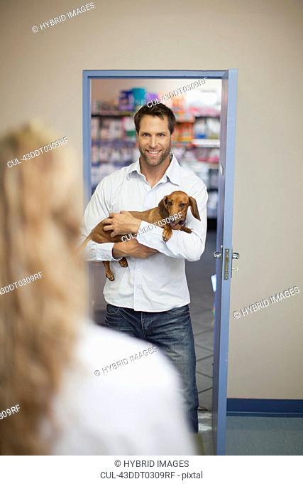 Man bringing dog to veterinarian