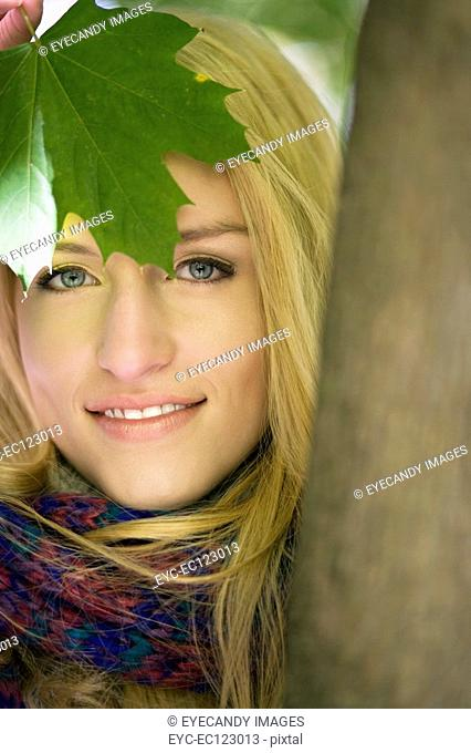 Portrait of young woman holding green leaf in autumn nature
