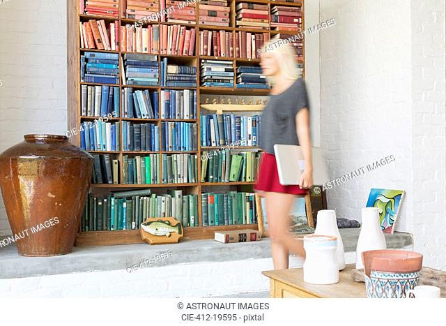 Blurred view of woman walking by book shelves
