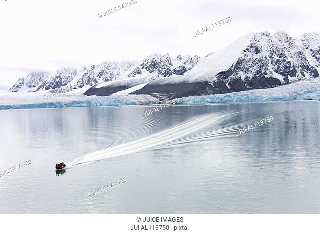 Polar circle boat with expedition participants cruising in front of Monacobreen glacier, Liefdefjorden, Haakon VII Land, Spitsbergen, Svalbard, Norway, Europe