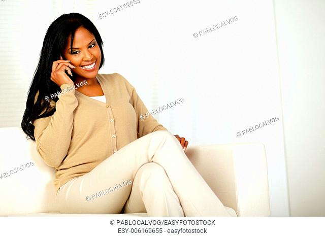 Portrait of a lovely young woman smiling and conversing on mobile phone while sitting on couch at home indoor