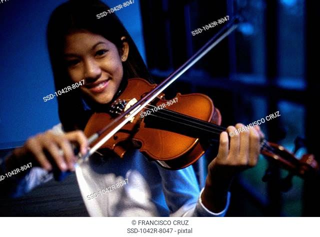 Portrait of a teenage girl playing the violin